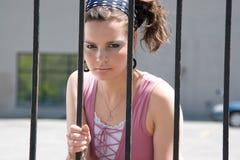 Fashion model behind iron bars Royalty Free Stock Image