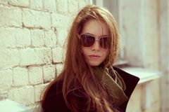 Fashion model in a black coat and sunglasses Stock Photos