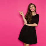 Fashion Model In Black Dress Pointing Royalty Free Stock Photography