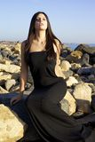 Fashion model with black dress sitting on rocks in front of sea Royalty Free Stock Photo