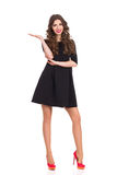 Fashion Model in Black Mini Dress Presenting Product. Beautiful woman in black mini dress standing with arm raised and presenting virtual product. Full length Royalty Free Stock Photography