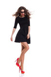 Fashion Model in Black Mini Dress and Red High Heels. Beautiful woman in sunglasses wearing black mini dress and red high heels standing on one leg. Full length Stock Photo