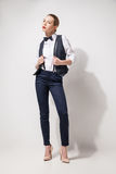 Fashion model in black trousers, top, bow tie and vest posing over white. Fashion model in black trousers and white top and vest posing over white backgroud stock images