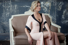 Fashion model with blond hair. Young attractive woman, siting on the sofa, vintage style Stock Images