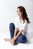 Fashion model in a blouse and jeans barefoot Royalty Free Stock Images