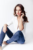 Fashion model in a blouse and jeans barefoot Stock Image