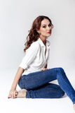 Fashion model in a blouse and jeans barefoot Royalty Free Stock Photos