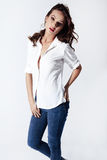 Fashion model in a blouse and jeans barefoot Royalty Free Stock Image