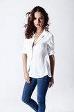 Fashion model in a blouse and jeans barefoot Royalty Free Stock Photo