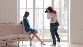 Fashion model in blue dress sits on sofa, photographer shoots her look stock video footage