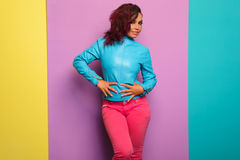 Fashion model in blue leather jacket, denim pants. Posing over Tricolor background.  Stock Image