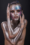 Fashion model with bright makeup and colorful glitter and sparkles on her face and body. Royalty Free Stock Photography