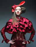 Fashion model in bright red costume and red hat Royalty Free Stock Images