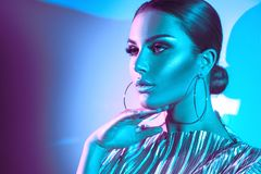 Fashion model brunette woman in colorful bright neon lights. Beautiful girl, trendy glowing makeup, metallic silver lips royalty free stock images