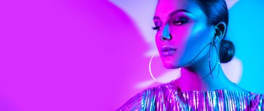 Fashion model brunette woman in colorful bright neon lights posing in studio. Beautiful girl, trendy glowing makeup. Metallic silver lips royalty free stock images