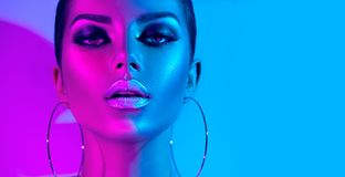 Fashion model brunette woman in colorful bright neon lights posing in studio. Beautiful girl, trendy glowing makeup royalty free stock image