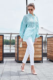 Fashion model brunette woman sexy pretty lady summer mood wear b. Lue blouse white jeans casual collection of clothes street look walk date romantic city perfect Stock Image
