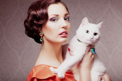 Fashion model with cat. Fashion model with make up hair style and jewelry holding white cat, vintage style stock photography