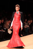 Fashion model catwalk red leather dress. Model showing the new fall/winter collection on the catwalk, wearing a long red leather dress during the milan fashion royalty free stock photography