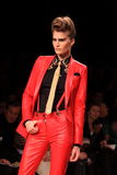 Fashion model on the catwalk - Copyspace. Model showing the new fall/winter collection on the catwalk, wearing a red leather pants and jacket during the milan Stock Photography