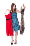 Fashion model with choice of dresses. Beautiful brunette fashion model with a choice of dresses which she is holding up on hangers isolated on white Stock Photography