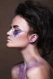 Fashion model with colorful make-up and blue glitter and sparkles on her face and body. Royalty Free Stock Image