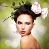Fashion model with creative hairstyle. Beautiful woman with pink flowers in hairs posing over creative color background. Fashion model with creative hairstyle royalty free stock images