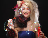 Fashion model with creative make-up blowing soap bubbles. Doll style Stock Photo