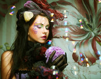 Fashion model with creative make-up blowing soap bubbles. Doll style Royalty Free Stock Photo