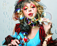 Fashion model with creative make-up blowing soap bubbles. Royalty Free Stock Image