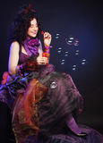 Fashion model with creative make-up blowing soap bubbles. Stock Photography