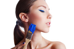 Fashion model with creative make up holding blue paintbrush Royalty Free Stock Image