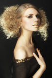 Fashion model with curly hair in black tunic. In black background stock photos