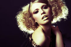 Fashion model with curly hair in black tunic. In black background stock photography