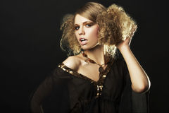 Fashion model with curly hair in black tunic Royalty Free Stock Images