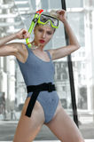 Fashion model demonstrates a diving mask with snorkel. She is dressed in a gray leotard and has blond hair. The concept of active life and water sports Royalty Free Stock Image