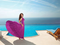Fashion Model Dress, Smiling Woman in Flowing Fabric purple Gown. Posing by the blue swimming pool, summer vacation. Luxury resort Royalty Free Stock Photography