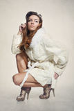 Fashion model in elegant white fur coat and gold shoes. Beautiful long-haired model posing in a white fur coat looking straight ahead Stock Photography