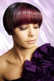 Fashion model with eyelash extensions. Portrait of a young model wearing a purple dress with short dark hair, looking down to show eyelash extensions Stock Images