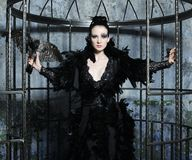 Fashion model in fantasy dress. Posing in steel cage royalty free stock images