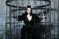 Fashion model in fantasy dress posing in steel cage. Woman in fantasy dress posing in steel cage royalty free stock photography