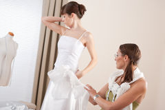 Fashion model fitting wedding dress by designer Royalty Free Stock Image