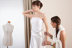 Fashion model fitting white dress by designer Stock Photos