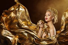 Fashion model in flying gold dress, golden woman beauty portrait royalty free stock images
