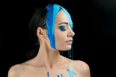 Fashion Model Girl colorful face paint. Beauty fashion art portrait of beautiful woman with flowing liquid paint, abstract makeup stock photo