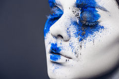 Fashion model girl portrait with colorful powder make up. woman with bright blue makeup and white skin. Abstract fantasy Royalty Free Stock Photo