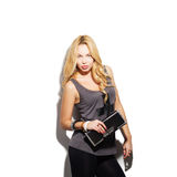 Fashion model girl portrait. Dressed in tight black pants, top and modern accessories holding clutch bag. Street fashion, casual style. Isolated on white Royalty Free Stock Photos