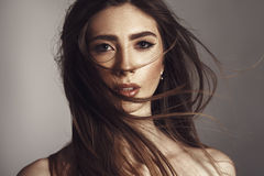 Fashion Model Girl Portrait with Long Blowing Hair. Close up portrait of young brunette woman with her hair in motion royalty free stock photos