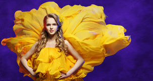 Fashion Model Girl in Yellow Dress, Young Woman in Flowing Fabric. Fashion Model Girl in Yellow Dress, Young Woman Posing in Flowing Fabric over Blue Studio Stock Images