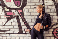 Fashion model in glam rock style on street. Near brick wall with graffiti Stock Images